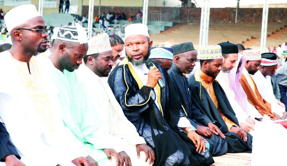 Mufti w'u Rwanda Sheikh Gahutu (ufashe mikoro) ayoboye amasengesho ku  munsi mukuru wa   wa  IDD EL Fitir kuri Sitade y'i Nyamirambo